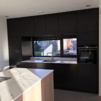 Wandvullende keukenkasten met kookeiland.